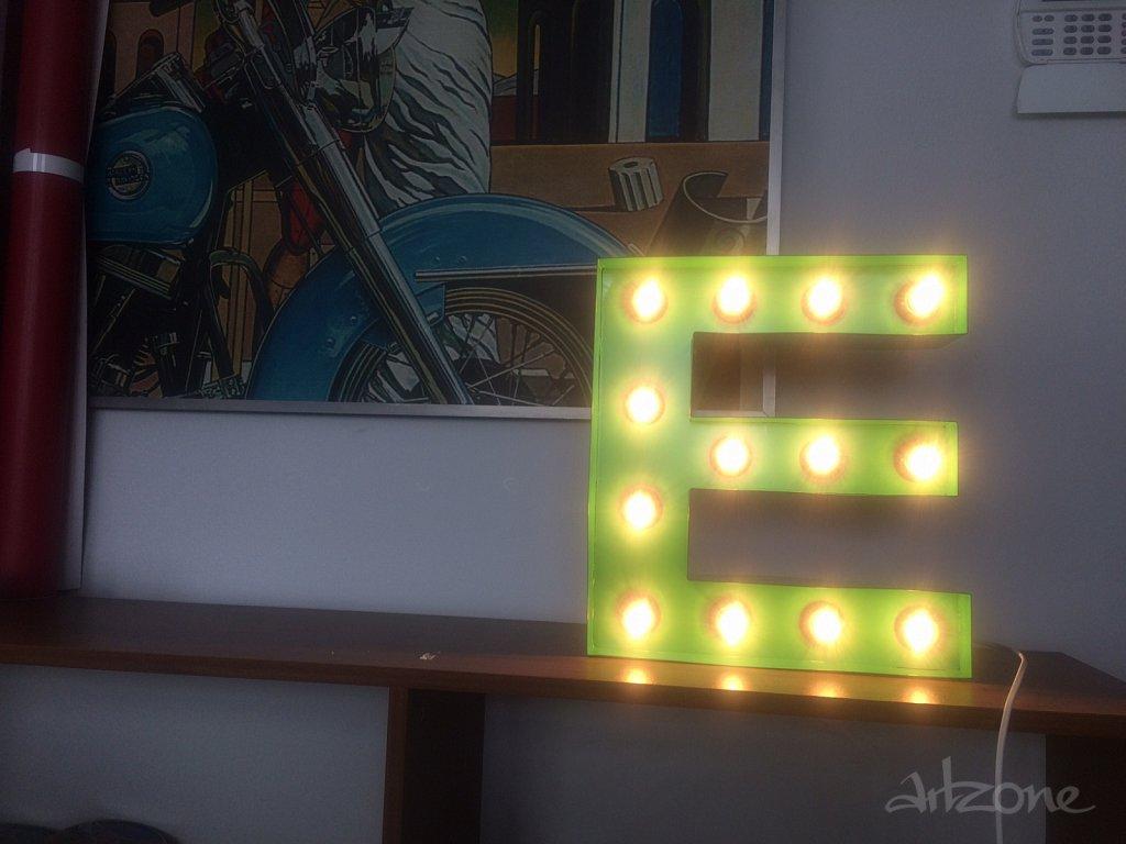 Светеща буква Е в зелено
